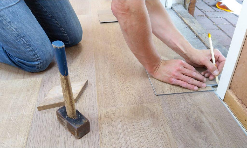 Homme qui pose du parquet pour rénover le sol de son salon