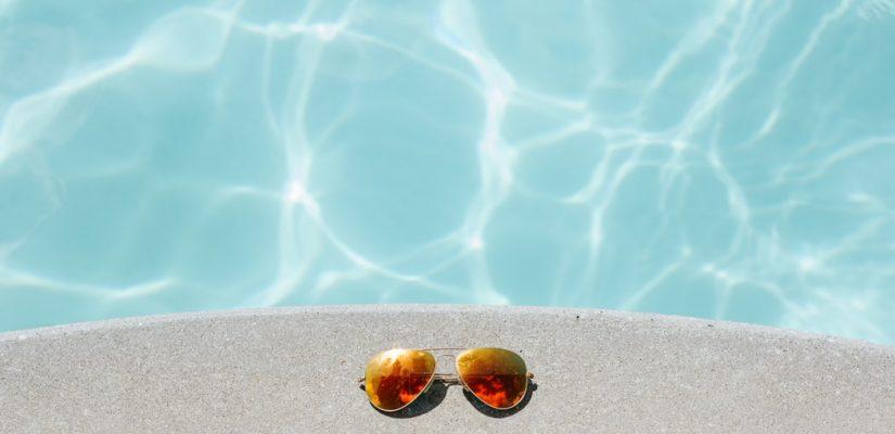 Paire de lunettes de soleil posée au bord d'une piscine