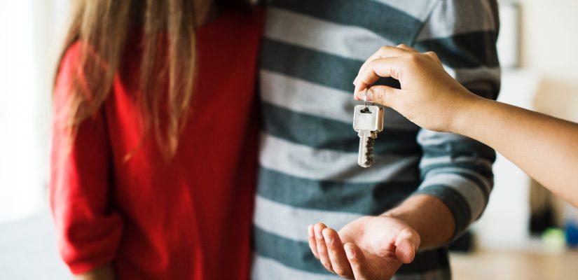 personne remettant des clés à un homme et une femme