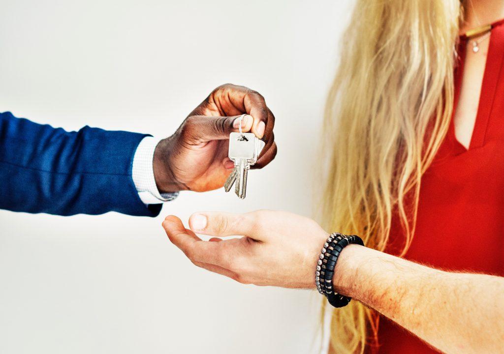 homme portant un costume bleu remettant des clés à une autre personne