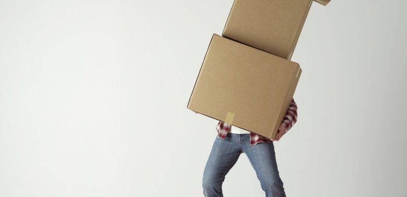 Personne qui soulève trois cartons de déménagement