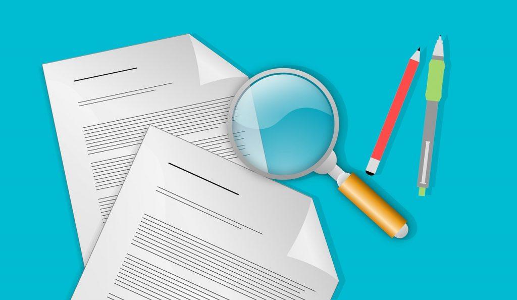 loupe et stylo posés à côté de deux documents papier