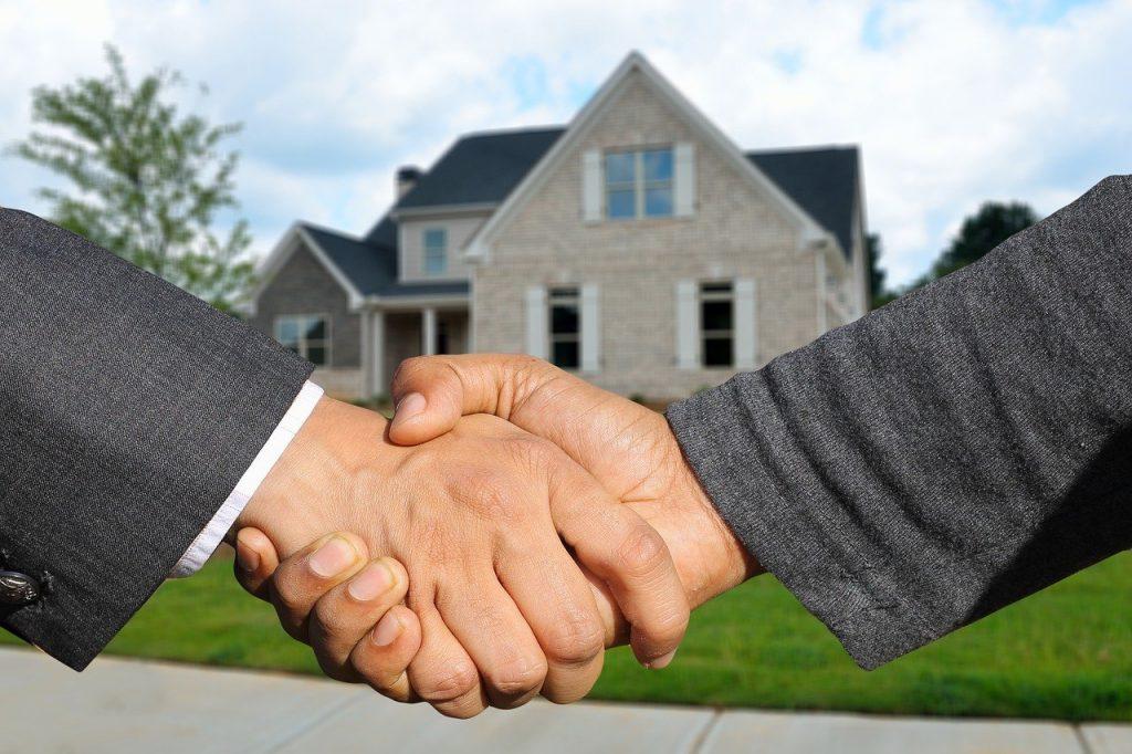 deux personnes qui se serrent la main devant une maison